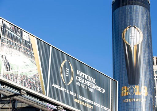 (Alyssa Pointer/Atlanta Journal-Constitution via AP). The Atlanta Westin hotel is decorated an image of the College Football Playoff National Championship Trophy, Friday, Jan. 5, 2018, in Atlanta. Georgia is to take on Alabama on Monday.
