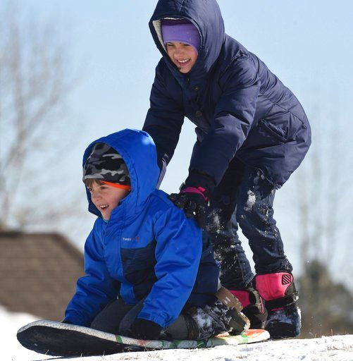 (Ken Blevins/The Star-News via AP). Cylie Echols pushes Matt Caracciolo down a small hill as they enjoy another day of sledding, Friday, Jan. 5, 2018 in Leland, N.C.