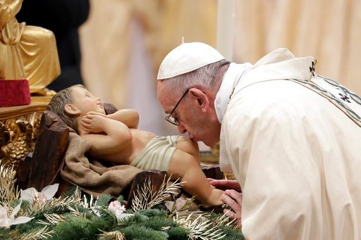 (AP Photo/Andrew Medichini). Pope Francis kisses a statue of the Divine Infant as he arrives to celebrate an Epiphany Mass in St. Peter's Basilica at the Vatican, Saturday, Jan. 6, 2018.