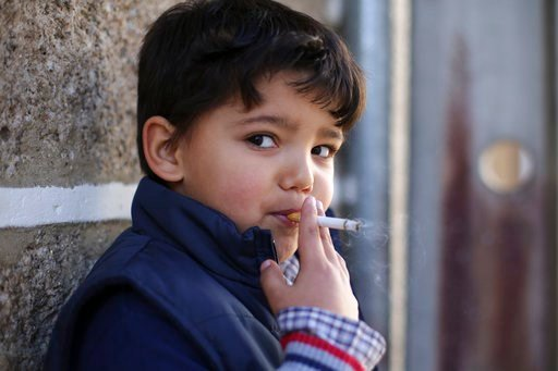 (AP Photo/Armando Franca). Fernando, 6-years-old, smokes a cigarette in the village of Vale de Salgueiro, northern Portugal, during the local Kings' Feast Saturday, Jan. 6, 2018. The village's Epiphany celebrations, called Kings' Feast, feature a tradi...