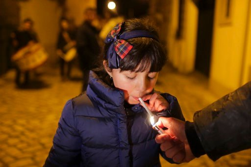 (AP Photo/Armando Franca). An adult helps a young girl light a cigarette as a band plays in the background in the village of Vale de Salgueiro, northern Portugal, during the local Kings' Feast Friday, Jan. 5, 2018. The village's Epiphany celebrations, ...