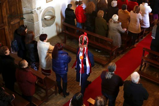 """(AP Photo/Armando Franca). Alexandre Taveira, wearing his """"king"""" crown, walks around the church during mass looking for a successor during the local Kings' Feast in the village of Vale de Salgueiro, northern Portugal, Saturday, Jan. 6, 2018. Each year ..."""