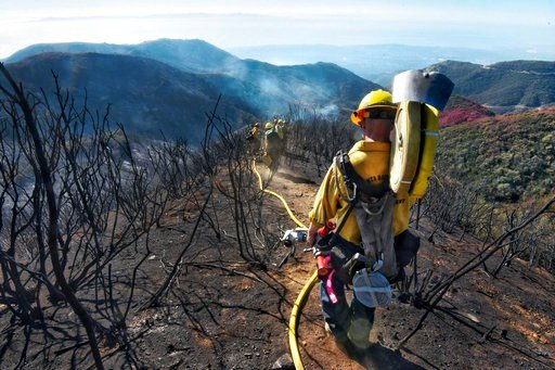 (Mike Eliason/Santa Barbara County Fire Department via AP, File). FILE - In this Dec. 19, 2017 file photo provided by the Santa Barbara County Fire Department, Santa Barbara County Firefighters haul dozens of pounds of hose and equipment down steep ter...