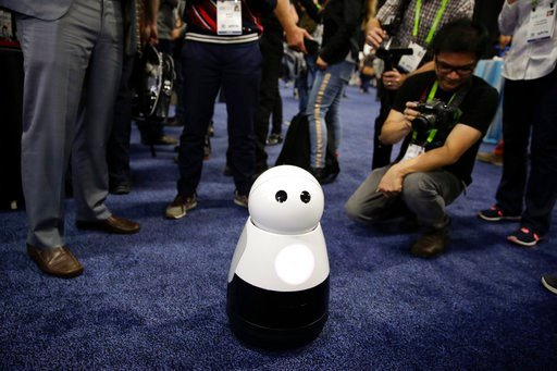 (AP Photo/Jae C. Hong). Mayfield Robotics' Kuri home robot is surrounded by attendees during CES Unveiled at CES International Sunday, Jan. 7, 2018, in Las Vegas.