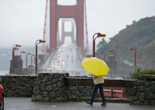 (AP Photo/Eric Risberg). A woman walks in the rain at a vista point with the Golden Gate Bridge in the background Monday near Sausalito, Calif. Storms brought rain to California on Monday and increased the risk of mudslides.