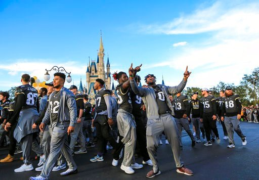 (Jacob Langston/Orlando Sentinel via AP). Central Florida football players celebrate during the a parade at Walt Disney World in the Magic Kingdom on Sunday, Jan. 7, 2018, in Orlando, Fla.