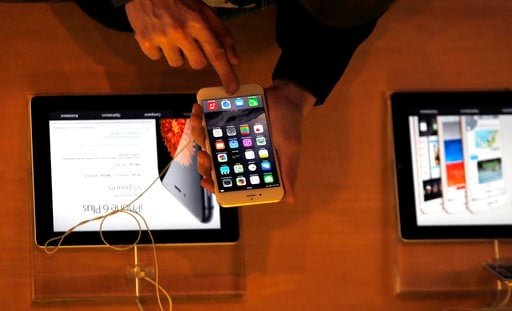 (AP Photo/Christophe Ena, File). FILE - In this Sept.19, 2014 file photo, a customer checks the iPhone 6, in Paris. A French prosecutor office said Tuesday Jan.9, 2018 an investigation into Apple over alleged planned obsolescence of some of its smartph...