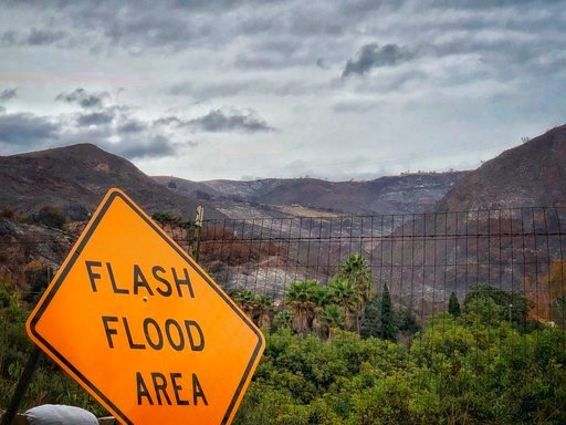 (Mike Eliason/Santa Barbara County Fire Department via AP). In this photo provided by Santa Barbara County Fire Department, a flash flood area sign is posted, as evacuations have been issued for several fire-ravaged communities in Santa Barbara, Calif....