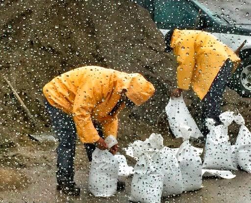 (Mike Eliason/Santa Barbara County Fire Department via AP). In this photo taken through a glass window, released by Santa Barbara County Fire Department, people fill up sandbags under the rain in Santa Barbara, Calif., Monday, Jan. 8, 2018. Storms brou...