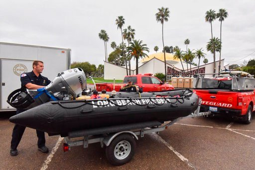 (Mike Eliason/Santa Barbara County Fire Department via AP). In this photo released by Santa Barbara County Fire Department, members of the Long Beach Fire Department Swift Water Rescue Team check equipment while staged at Earl Warren Showgrounds in San...