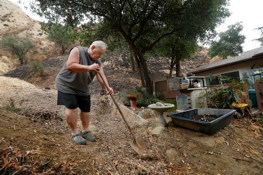 (Mel Melcon/Los Angeles Times via AP). Bill Susel, 77, removes debris from a gully in back of his home on Spring Trail in Kagel Canyon, in preparation for expected heavy rains later tonight, Monday, Jan. 8, 2018.