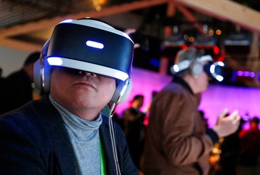 (AP Photo/John Locher). People look through Sony PlayStation VR headsets after a Sony news conference at CES International, Monday, Jan. 8, 2018, in Las Vegas.