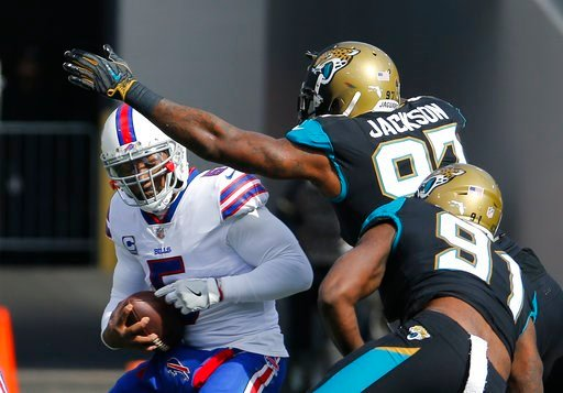 (AP Photo/Stephen B. Morton). Buffalo Bills quarterback Tyrod Taylor, left, is sacked by Jacksonville Jaguars defensive tackle Malik Jackson, center, and defensive end Yannick Ngakoue (91) in the first half of an NFL wild-card playoff football game, Su...