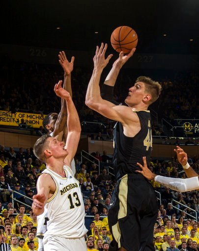 (AP Photo/Tony Ding). Purdue center Isaac Haas shoots over Michigan forward Moritz Wagner (13) during the first half of an NCAA college basketball game at Crisler Center in Ann Arbor, Mich., Tuesday, Jan. 9, 2018.