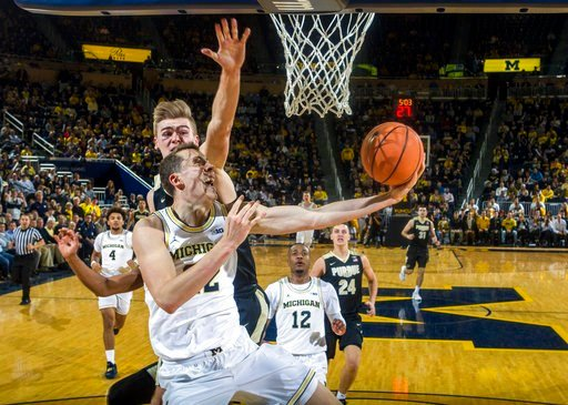 (AP Photo/Tony Ding). Michigan guard Duncan Robinson, front, goes to the basket against Purdue forward Matt Haarms during the first half of an NCAA college basketball game at Crisler Center in Ann Arbor, Mich., Tuesday, Jan. 9, 2018.