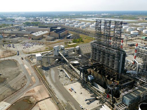 (DroneBase via AP, File). FILE - In this Sept. 21, 2017 file photo, petroleum coke, the grainy black byproduct of refining Canadian tar sands oil, is visible at the BP Whiting refinery in East Chicago, Ind. New York City officials say they will begin t...