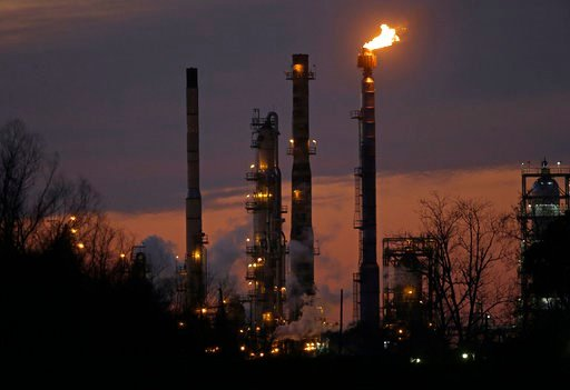 (AP Photo/Gerald Herbert, File). FILE - In this Feb. 13, 2015 file photo, stacks and burn-off from the ExxonMobil refinery are seen at dusk in St. Bernard Parish, La. New York City officials say they will begin the process of dumping about $5 billion i...