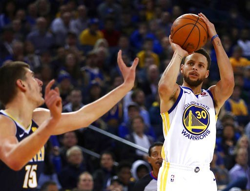 (AP Photo/Ben Margot). Golden State Warriors' Stephen Curry, right, shoots against Denver Nuggets' Nikola Jokic (15) during the second half of an NBA basketball game Monday, Jan. 8, 2018, in Oakland, Calif. Golden State won, 124-114.