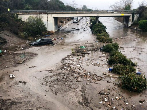 (Mike Eliason/Santa Barbara County Fire Department via AP). In this photo provided by Santa Barbara County Fire Department, U.S. Highway 101 at the Olive Mill Road overpass is flooded with runoff water from Montecito Creek in Montecito, Calif.