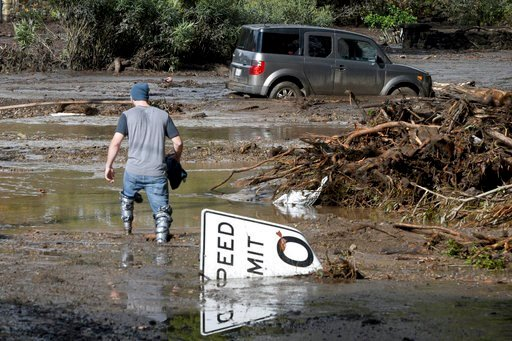 (AP Photo/Michael Owen Baker). Mitchell Barrett crosses mud from an overflown creek on Sheffield Drive in Montecito, Calif., following the heavy rain, Tuesday, Jan. 9, 2018. Barrett was going to check on his parents' house in Montecito.