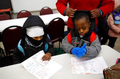 (AP Photo/Patrick Semansky). In this Jan. 9, 2018 photo, teacher Loraine Wilson, top right, helps bundle up pre-kindergarten students as they wait to be picked up at the end of a school day at Lakewood Elementary School in Baltimore. The recent spell o...