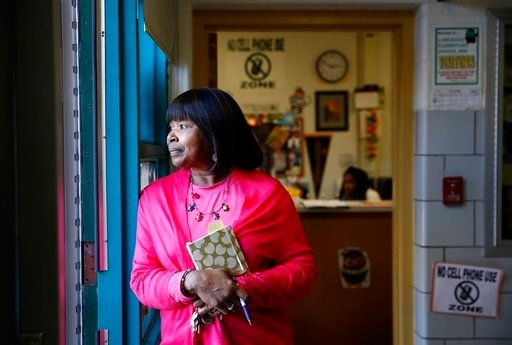(AP Photo/Patrick Semansky). In this Jan. 9, 2018 photo, Principal Teresa Hall-Cooper looks out the front door at Lakewood Elementary School in Baltimore as parents arrive to pick up their children at the end of the school day. At Lakewood, a 1960s-era...