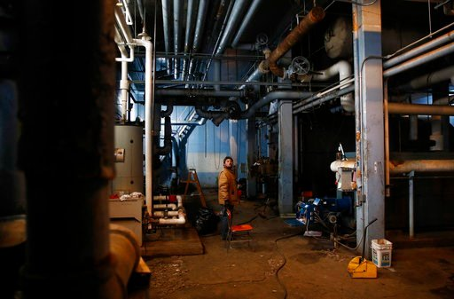 (AP Photo/Patrick Semansky). In this Jan. 8, 2018 photo, a worker stands in an underground boiler room at the Calverton Elementary-Middle School in Baltimore. Bitterly cold weather lead to busted pipes at the school, prompting a shutdown of the main bo...
