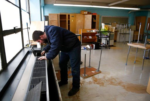 (AP Photo/Patrick Semansky). In this Jan. 8, 2018 photo, a worker inspects a heating and cooling unit in a classroom at Calverton Elementary-Middle School in Baltimore. Bitterly cold weather lead to busted pipes at the school, prompting a shutdown of t...