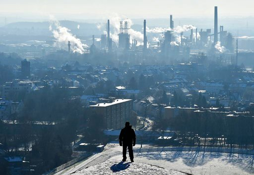 (AP Photo/Martin Meissner, File). FILE - In this Jan. 19, 2016 file photo, a man watches a BP refinery in Gelsenkirchen, Germany. New York City officials say they will begin the process of dumping about $5 billion in pension fund investments in fossil ...