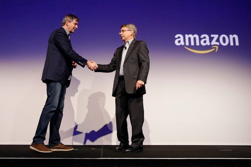 (AP Photo/Jae C. Hong). Tom Gebhardt, right, chairman and CEO of Panasonic Corp. of North America, shakes hands with Amazon's Tom Taylor after watching a presentation during a news conference at CES International, Monday, Jan. 8, 2018, in Las Vegas.