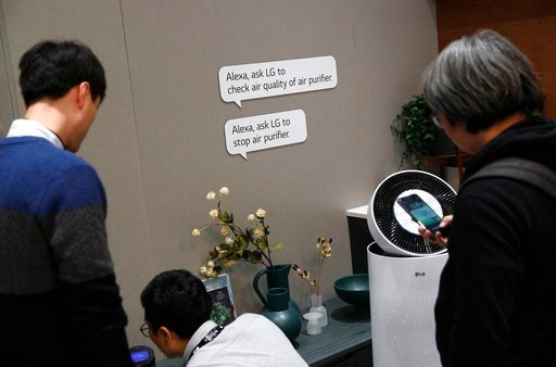 (AP Photo/John Locher). People look at home appliances that can be controlled by Amazon's Alexa at the LG booth during CES International, Tuesday, Jan. 9, 2018, in Las Vegas.
