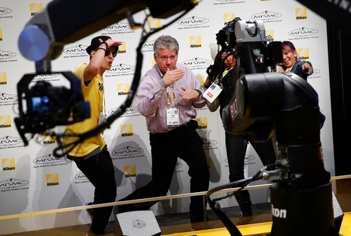 (AP Photo/John Locher). Kirk Clyatt, center, dances for remote cameras at the Nikon booth during CES International, Tuesday, Jan. 9, 2018, in Las Vegas.