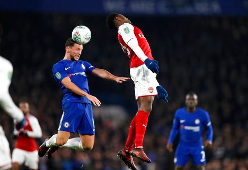 (AP Photo/Kirsty Wigglesworth). Chelsea's Danny Drinkwater jumps for the ball with Arsenal's Danny Welbeck, right, during the English League Cup semifinal, first leg, soccer match between Chelsea and Arsenal at Stamford Bridge stadium in London, Wednes...