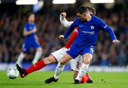 (AP Photo/Kirsty Wigglesworth). Chelsea's Eden Hazard vies for the ball with Arsenal's Shkodran Mustafi, background, during the English League Cup semifinal, first leg, soccer match between Chelsea and Arsenal at Stamford Bridge stadium in London, Wedn...