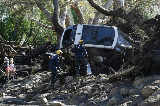 (AP Photo/Marcio Jose Sanchez). Members of the Los Angeles County Fire Department Search and Rescue crew work on a car trapped under debris in Montecito, Calif., Wednesday, Jan. 10, 2018. Dozens of homes were swept away or heavily damaged and several p...