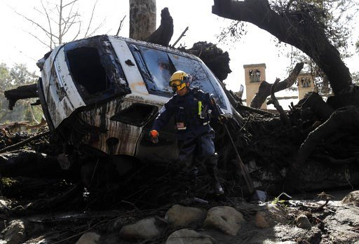 (AP Photo/Marcio Jose Sanchez). A member of the Los Angeles County Fire Department Search and Rescue crew works near a car trapped under debris in Montecito, Calif., Wednesday, Jan. 10, 2018. Dozens of homes were swept away or heavily damaged and sever...