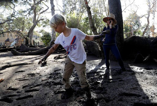 (AP Photo/Marcio Jose Sanchez). Jennifer Markham, right, and her son Peter walk in mud in Montecito, Calif., Wednesday, Jan. 10, 2018. Dozens of homes were swept away or heavily damaged and several people were killed Tuesday as downpours sent mud and b...