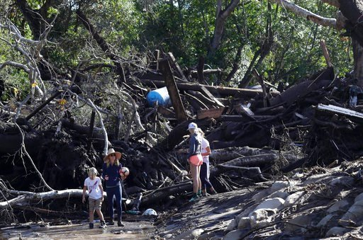 (AP Photo/Marcio Jose Sanchez). Jennifer Markham, second from left, walks under damaged trees with her children and a family friend in Montecito, Calif., Wednesday, Jan. 10, 2018. Dozens of homes were swept away or heavily damaged and several people we...