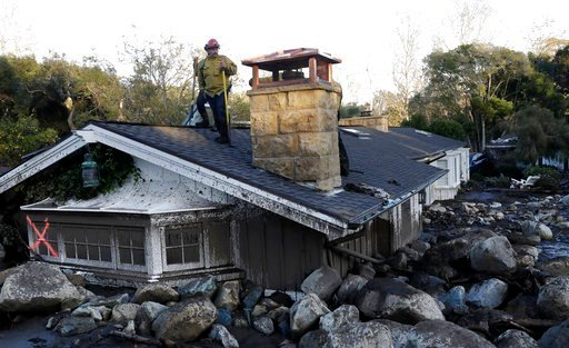 (AP Photo/Marcio Jose Sanchez). A firefighter stands on the roof of a house submerged in mud and rocks Wednesday, Jan. 10, 2018, in Montecito, Calif. Anxious family members awaited word on loved ones Wednesday as rescue crews searched grimy debris and ...