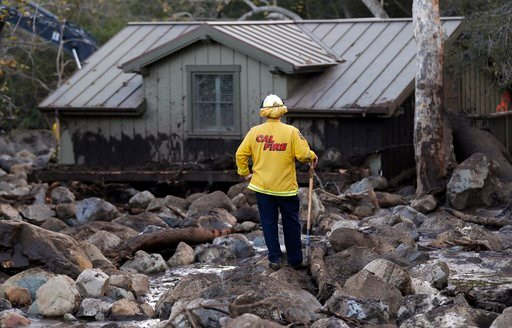 (AP Photo/Marcio Jose Sanchez). A firefighter walks among the rocks and mud left by a mudslide Wednesday, Jan. 10, 2018, in Montecito, Calif.