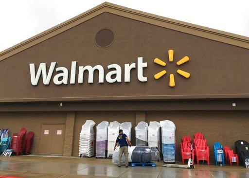 (AP Photo/Elise Amendola, File). FILE - In this June 5, 2017, file photo, a worker stacks merchandise outside a Walmart in Salem, N.H. Walmart is boosting its starting salary for U.S. workers to $11 an hour, giving a one-time $1,000 cash bonus to eligi...