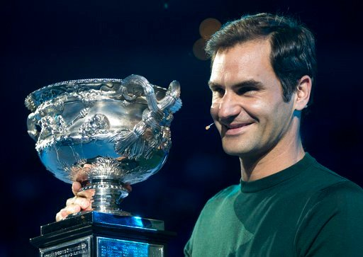 (AP Photo/Mark Baker). Defending men's singles champion Switzerland's Roger Federer poses for a photo with his trophy during a ceremony for the official draw at the Australian Open tennis championships in Melbourne, Australia Thursday, Jan. 11, 2018.