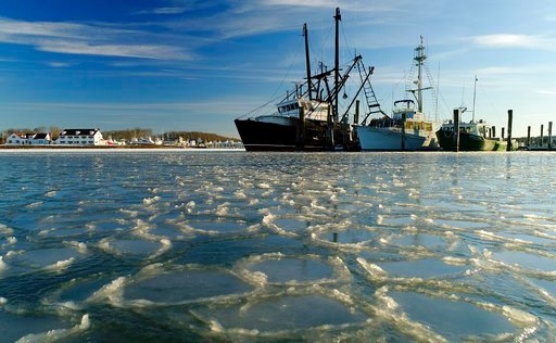 (AP Photo/Julie Jacobson, File). FILE - In this Jan. 7, 2018, file photo, fishing trawlers sit on the frozen harbor of Lake Montauk surrounded by thin sheets of ice in Montauk, N.Y. A quick study of the brutal American cold snap found that the Arctic b...