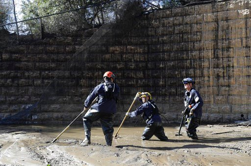 (AP Photo/Marcio Jose Sanchez). Members of the Los Angeles County Fire Department Search and Rescue crew work in mud and flooded waters in Montecito, Calif., Wednesday, Jan. 10, 2018. Dozens of homes were swept away or heavily damaged and several peopl...