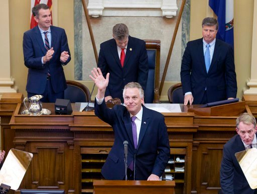 (AP Photo/Steve Helber). Virginia Gov. Terry McAuliffe waves to the gallery as he addresses a joint session of the the 2018 session in the House chambers at the Capitol in Richmond, Va., Wednesday, Jan. 10, 2018. Gov.-elect Lt. gov. Ralph Northam, top ...