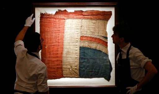 (AP Photo/Frank Augstein). Sotheby's employees look at a frame with a fragment of a Union Jack in London, Thursday, Jan. 11, 2018. An exceptionally large fragment of the Union Flag, which flew from HMS Victory at the Battle of Trafalgar and Love Letter...