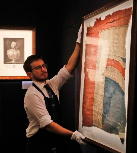 (AP Photo/Frank Augstein). A Sotheby's employee adjusts a frame with a fragment of a Union Jack in London, Thursday, Jan. 11, 2018. An exceptionally large fragment of the Union Flag, which flew from HMS Victory at the Battle of Trafalgar and Love Lette...