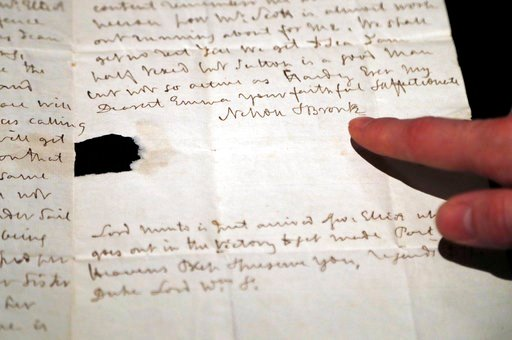 (AP Photo/Frank Augstein). A Sotheby's employee points to a signature of Lord Nelson on a letter at Sotheby's auction house in London, Thursday, Jan. 11, 2018. An exceptionally large fragment of the Union Flag, which flew from HMS Victory at the Battle...