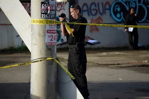 (AP Photo/Carlos Giusti). A forensic worker photographs a crime scene where a man was found fatally shot, in San Juan, Puerto Rico, Thursday, Jan. 11, 2018. Thirty-two people have been slain in Puerto Rico in the first 11 days of the year, double the n...