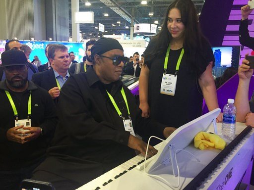 "(AP Photo/Matt O'Brien). In this Wednesday, Jan. 10, 2018, photo, musician Stevie Wonder plays a so-called ""smart"" piano, an internet-connected device designed to teach people how to play, while piano teacher Gabie Perry stands next to him at The One M..."